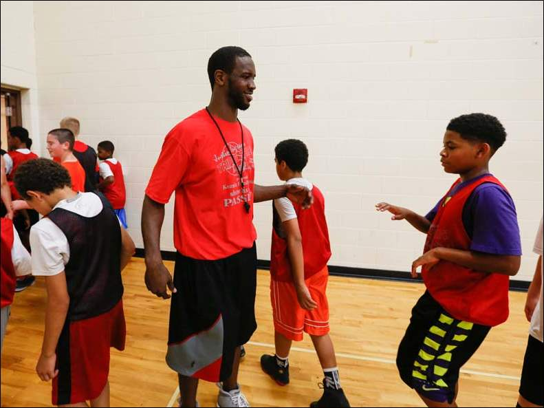 Justin Ingram greets campers as they come off the court for a break during his Triple Threat Basketball Camp at Waverly High School in Lansing on July 7.