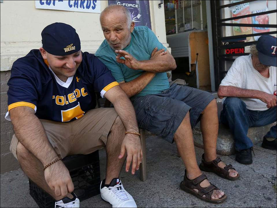 Radi Chieab, left, listens to his father Hassan, 82, center, as they joke with their neighbor Kenneth Berry, right, outside Bush Carry Out in Toledo's North End.