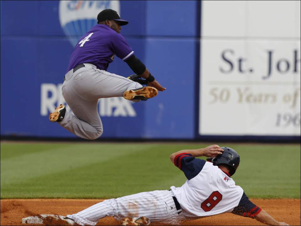 Louisville Bats player Irving Falu (4) turns the double play after forcing out Toledo Mud Hens player Josh Wilson (8) during the third inning.