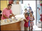 Casey Sargent, left, helps a line of children get their tray of food during a free summer lunch at the Speckled Frog Learning Center in Monroe last week.
