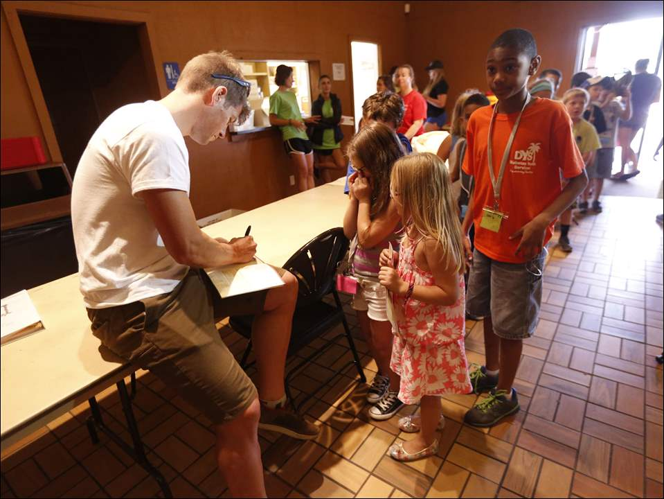 Olympic athlete Kris Freeman, left, a cross country skier who has competed in the Olympics three times, and who has Type I diabetes, signs autographs for campers Addy Tabb, 8, left, of Toledo, and Madison Fellers, 7, right, of Toledo, during Little Shots Day Camp at Olander Park on Tuesday. The week-long camp is designed especially for children who have Type 1 diabetes. Camper Isaiah Miller, 9, of Toledo, far right, waits his turn.