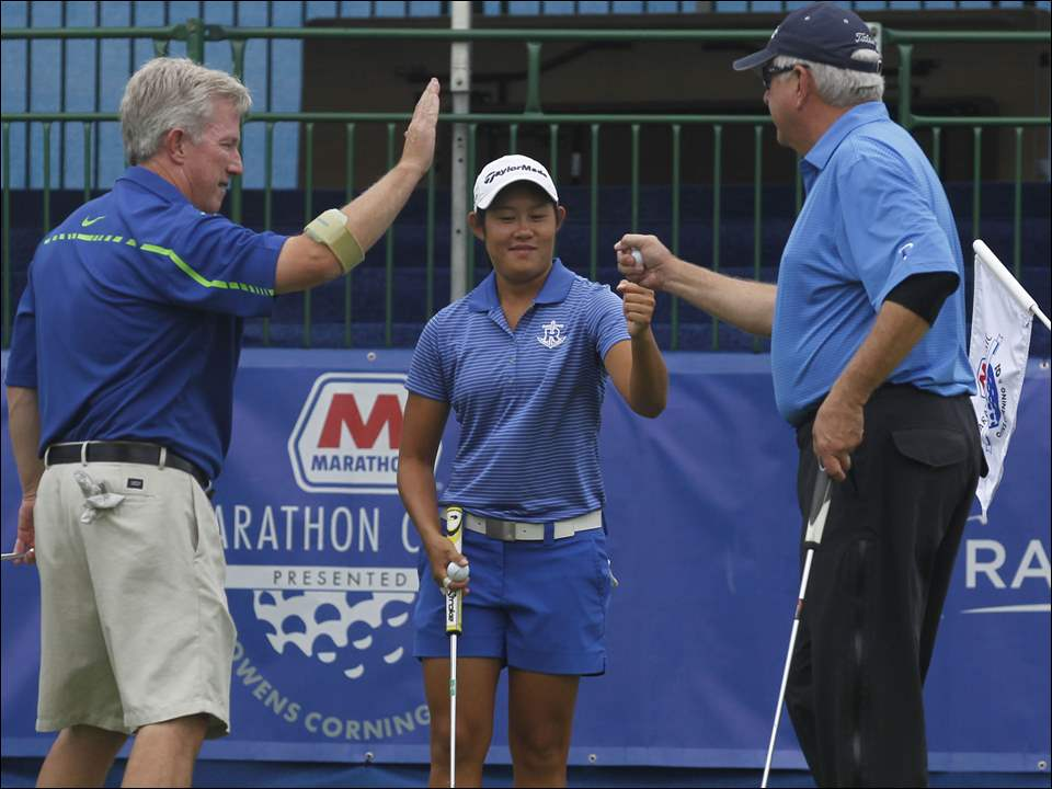 LPGA pro Sandra Changkija is high-fived by Mike Hart, left, and Rick Robertson during the 2015 ProMedica/Hylant Pro-Am at Highland Meadows Golf Course in Sylvania.