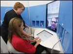 Brittany Rains, standing, a ProMedica Physicians Group medical assistant, and Kayla Lewandowski, an intern at ProMedica, test the HealthSpot video-conference kiosk with Dr. George N. Darah at the pharmacy on the ProMedica Toledo Hospital campus.