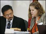 Dr. Ray Estacio, left, a member of the Colorado Board of Health, confers with Deborah Nelson, board administrator, during testimony Wednesday in Denver.