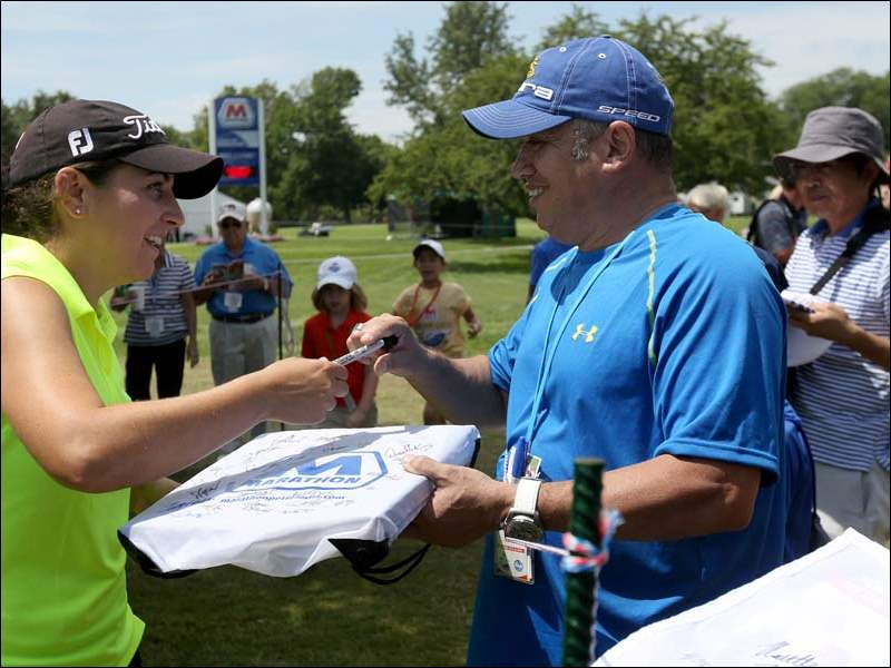 LPGA golfer Nannette Hill, left, signs an autograph for West Toledo resident Rafael Aponte, right, after solidifying herself as a co-leader with four under par during the first round of the Marathon Classic.