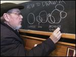 Wes Booher demonstrates how to draw Mickey Mouse, starting with shapes, at a restaurant in Dundee. 'This is the quintessential him doing what he loved to do best,'  said his wife, Libby, who took the photo. 'That is his teaching style, his easy-to-draw technique, Wes Booher-style.'