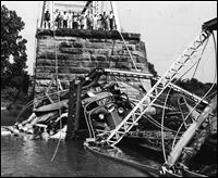 The twisted wreckage of the span of the Waterville bridge which collapsed yesterday is shown. The span, second of the bridge on the eastern side, gave way as a heavily-laden milk truck was passing over it. The driver and his helper were severely bruised and shaken. The crushed truck is shown wrapped in the wreckage. Toledo Times file photo dated July 24, 1941.