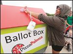 Raven Pennington, 21, of Cincinnati, casts her ballot for her favorite Pizza during the annual Pizza Palooza at Centennial Terrace in July, 2014.