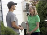 Sandy Drabik Collins talks with South Toledo resident Ian Gagnon as she goes door to door Wednesday.