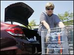 Lynn Duty of Toledo puts packages of bottled water in her car on Tuesday at The Anderson's on Talmadge Road in Toledo, Ohio. The water safety level is at 'watch.'