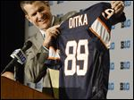 Michigan coach Jim Harbaugh shows off a Mike Ditka throwback jersey during the Big Ten's media days on Friday in Chicago. Ditka coached Harbaugh during his time with the Chicago Bears.