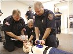 From left, Bill Montrie, Lynda Bennett, and Michael Cook of the Springfield Township Fire Department demonstrate CPR techniques last month.