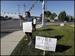 Bradley Hashim, foreground, and Christine Handwork wave to drivers and hold signs saying 'Honk for Happiness' and 'Smile' on the corner of Secor Road and Central Avenue on Sunday.