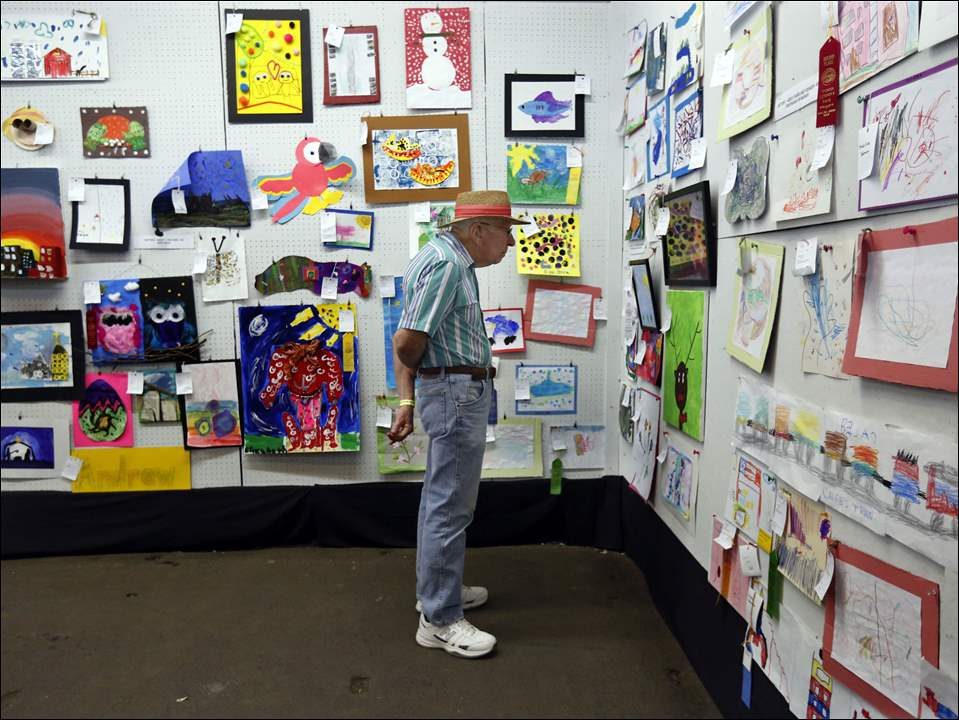 Bill Rock, from Bowling Green, looks at the art on exhibition during the Wood County Fair at the Wood County Fair Grounds in Bowling Green on Tuesday.