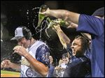 Mike Hessman, left, is doused with champagne after setting the all-time minor league record for most home runs by hitting No. 433 Monday night.