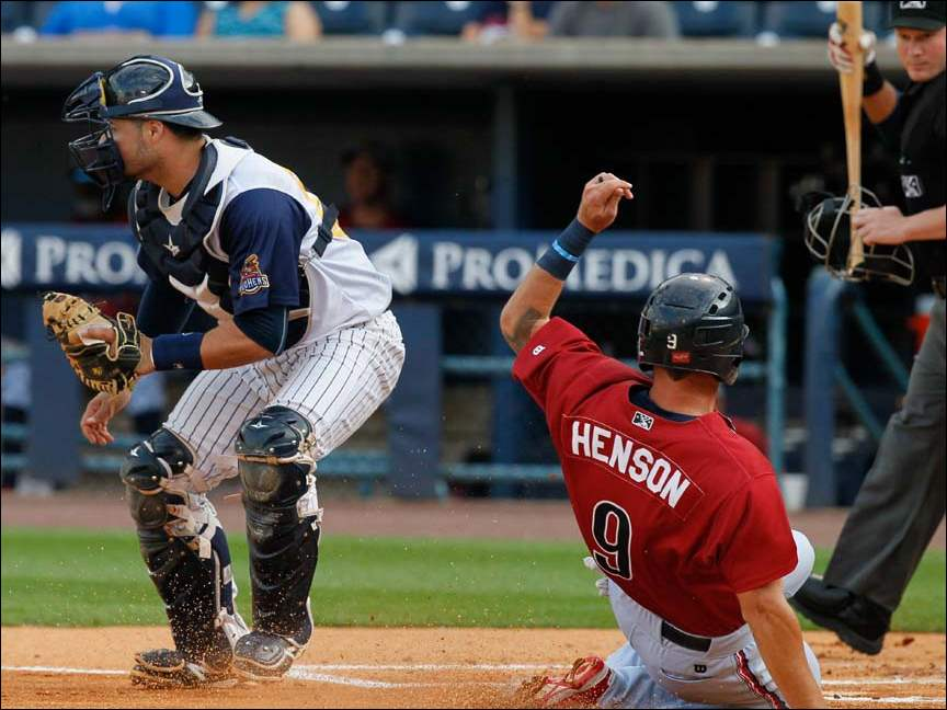 Lehigh Valley's Tyler Henson scores against Toledo catcher Manny Pina during the first inning.