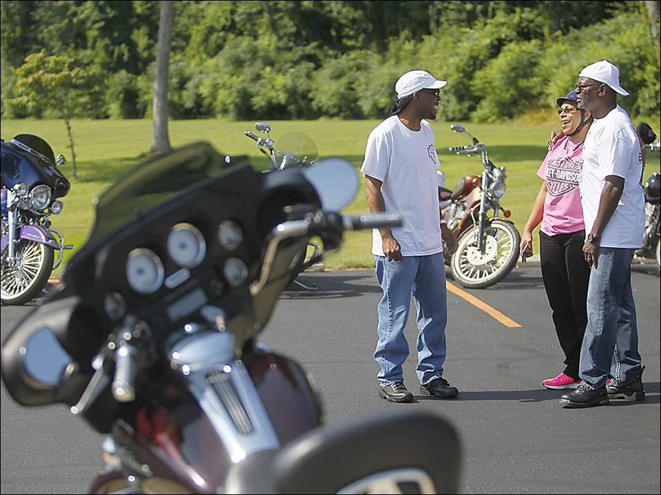 Kevin and Janice Staples of Toledo and Mitch Milton of Holland chat during the Ride for Kids Sake to benefit the Big Brothers Big Sisters at the Toledo Harley Davidson in Toledo on July 25.
