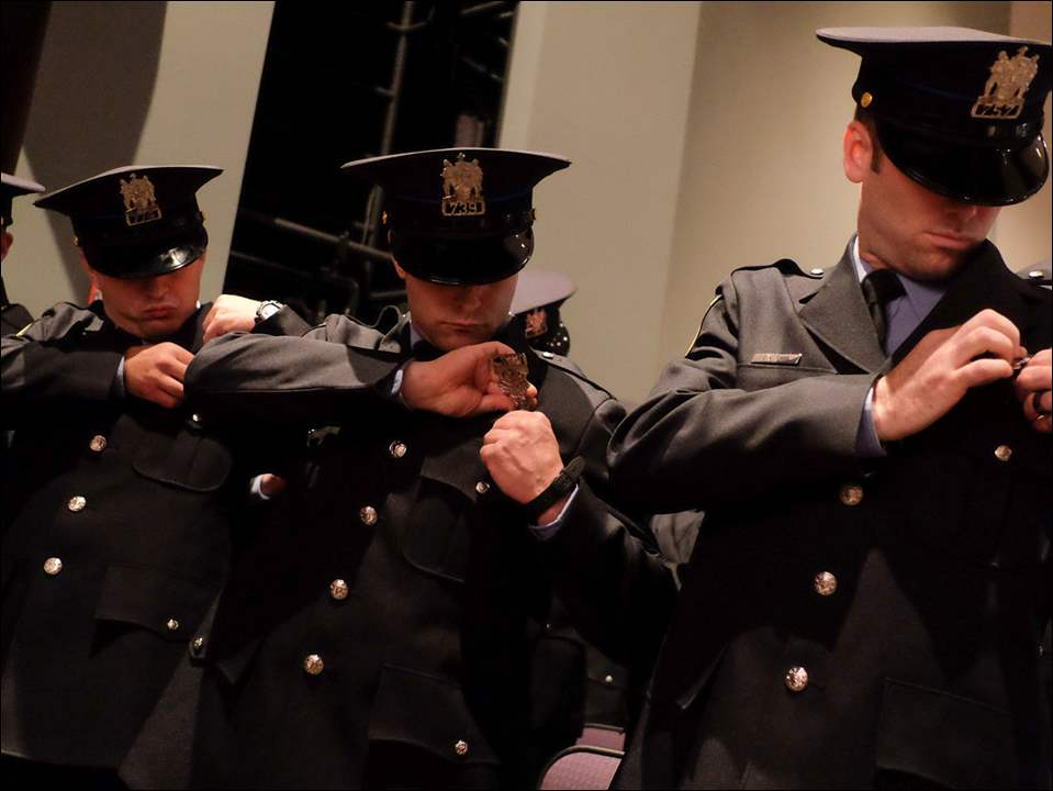 Left to right Officers Derek Adams, Daniel Balon, Jeffrey Breeze, and Jonathan Chio pin their badges during  the 62nd Toledo Police Academy Graduation Thursday.