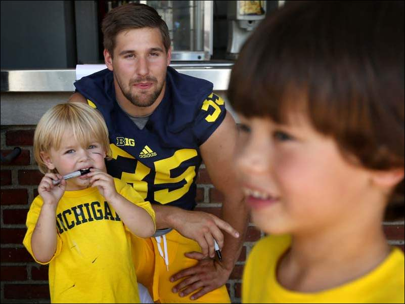 Michigan's Joe Bolden (35) smiles as he signs autographs for brothers Evan, 3, left, and Colin McBride, 5, during the Wolverine's football media day Thursday.