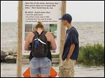 Jamie Shiple, left, and her son, Clayton Landers, both of Goodyear, Ariz., check a warning sign for algal toxins along the Lake Erie beach at Maumee Bay State Park in Jerusalem Township, Ohio, on Saturday.