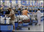 Shoppers check out at a Wal-Mart Supercenter store in Springdale, Ark.