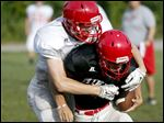 Bedford's Joey Weimer, left, attempts to tackle teammate Jared Nanney. They were in a varsity football scrimmage at the high school on Saturday. The teams' first day of full-contact practice was Friday.