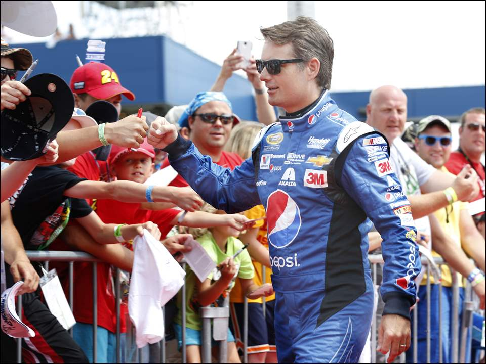 Jeff Gordon fist bumps a fan on his last walk on the red carpet for the Pure Michigan 400 at Michigan International Speedway on Sunday.
