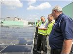 Plant manager Joe Choate, right, speaks with Ohio EPA Director Craig Butler, center, and  site utilities manager Tom Wynn about the solar panels installed on the roof of the Alexis Road plant, which received the state EPA's highest award for environmental stewardship.