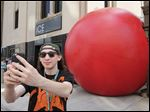 Slug: CTY redball  THE BLADE/JEREMY WADSWORTH    Caption: Shane Hartford of Toledo takes a selfie with the Red Ball Wednesday, 08/18/15, in front of ICE on Madison Street in Toledo, Ohio.