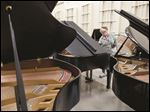 Virginia Luce, Perrysburg, shops for pianos during a sale at the University of Toledo Center for Performing Arts.