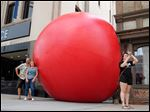 At left, RedBall artist Kurt Perschke poses with ICE Restaurant & Bar owner Donna Weisner for people taking pictures as Starr Jarvis takes a selfie with the Red Ball Wednesday on Madison Street in Toledo, Ohio.