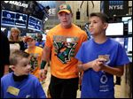 World Wrestling Entertainment superstar John Cena is accompanied by Make-A-Wish participants Evan Maher, left, and Elijah Mendoza as he visits the trading floor before ringing the New York Stock Exchange opening bell.
