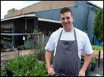 Chef Chris Nixon next to some of the herbs they grow for the restaurant Element 112.