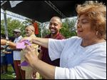 Toledo Public Schools Superintendent Romulus Durant, second from right, and  Toledo City Councilman Cecelia Adams, right, release Monarch butterflies, which symbolized the rebirth and resurrection of the Dorr Street community.