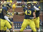 Whitmer graduate Chris Wormley, 43, celebrates a quarterback sack with Michigan teammates last season.