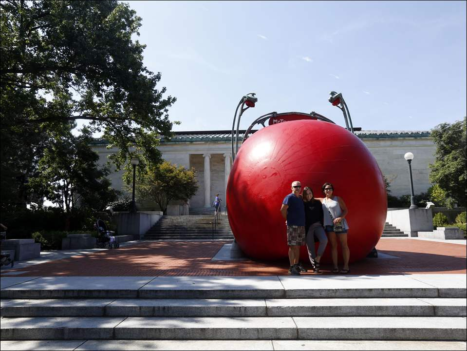 Tommy Hickman, left, Tatum Hickman, center, and Jodie Hickman, from Toledo, have their picture taken in front of the Red Ball Project at the Toledo Museum of Art Peristyle Terrace on August 23, 2015.