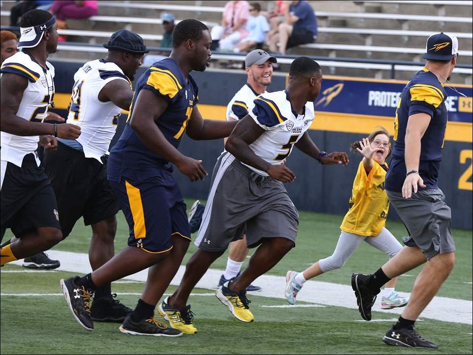 Bridget Allen, 9, sister of University of Toledo WR  Liam Allen, out runs the Toledo defense to score a touchdown during Victory Day.