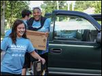 Stephanie Fuller, 22, a senior from Toledo, left, and Zay Cohen, 22, a senior from Washington, help to unload a new student's boxes during freshman move-in day on Thursday at Lourdes University in Sylvania.