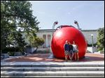 Tommy Hickman, left, Tatum Hickman, center, and Jodie Hickman, all of Toledo, pose for a picture with the RedBall at the Toledo Museum of Art on its final day in the city.
