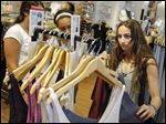 Giulia Pugliese, 15, shops for clothes with friends at Roosevelt Field mall in Garden City, N.Y. Teens are shopping like their parents this summer during the back-to-school season. Today's children recycle more clothes from the previous school year, they shop year-round for things, and when they do buy, they're less likely to purchase anything that's not on sale.