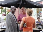 Former Toledo Mayor Mike Bell speaks with Lou Stefanoni and Melanie Davis during an event Thursday on the patio at Bar Louie.