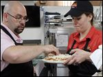 Trainer Chuck Blevins of Lincoln Park, Mich., spreads cheese on a pizza held by Sara Ragsdale of Charleston, S.C., in Marco's new test kitchen on Monroe Street. Marco's was named the second-fastest growing chain in the nation.
