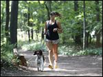 Caitlin Scannell runs on a trail in Wildwood Preserve Metropark with Abby. Ms. Scannell avoids processed foods 90 to 95 percent of the time and follows a workout routine that combines resistance training and cardiovascular exercise.