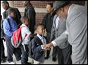 Jaylan Hamilton, an incoming sixth grader, left, with Larry Sykes, Toledo City Council member. Local professional, religious, business, and education leaders lineup outside of Martin Luther King, Jr., Academy for Boys to greet the students and welcome them to the first day of school with a handshake and a smile.