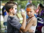 Aiden Cousino, 6, spaints tiger on the face of his cousin Jacob Cousino, 6, during the Barrio Latino Art Festival.
