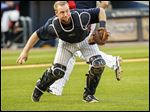 Mud Hens catcher Bryan Holaday picks up the bunted ball from the bat of Indianapolis batter Keon Broxton in the third inning. Holaday threw Broxton out at first.