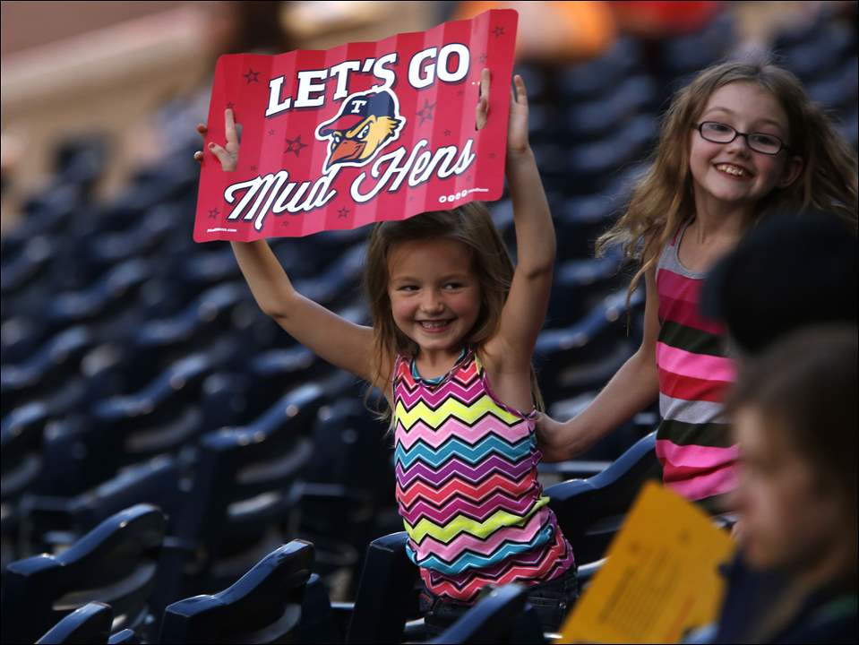 Toledo Mud Hens fan Taylor Johnson, 5, left, and her older sister Hayden Johnson, 7, of Maumee, cheer for the Hens.