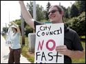 Sean Nestor hold a sign against fast tracking during a protest at the corner of Monroe and Secor Streets on Monday.