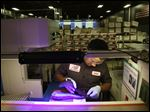 Elder Brandao, working under ultraviolet lights, glues an outsole to a midsole of the New Balance proposed 950v2 sneaker that has passed military testing at one of company's manufacturing facilities in Boston.