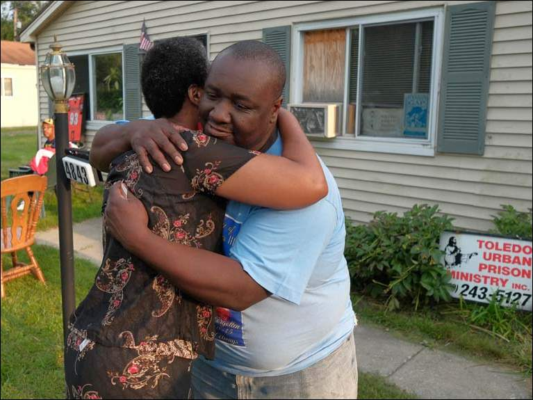 Johnny Jones Jr., father of Johnny Jones III, 14, and Joscelyn Jones, 16, gets a hug from family friend Debra Scott during a vigil for his children at his home, Thursday.